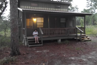A lone girl sits on the steps of her cabin.