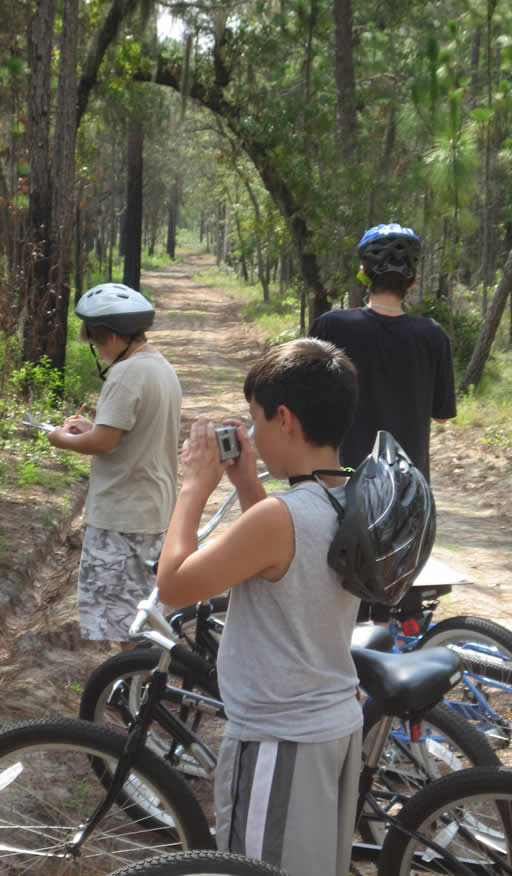 Three campers taking photos on a bike tour.